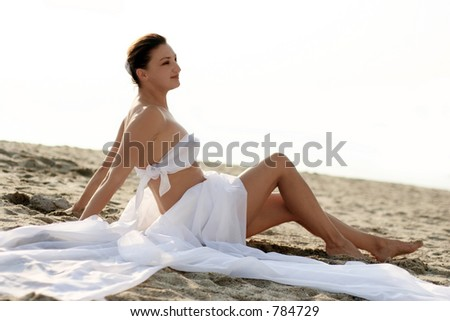 Woman in white clothes sitting on the beach - stock photo