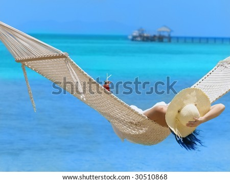 woman in white dress and hat on the beach with cocktail - stock photo