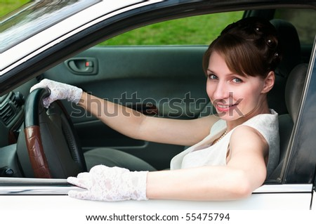 Woman in white dress and white-gloved sitting in car as a driver. Looking at camera