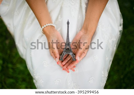 Woman in white dress holding a figurine of the Eiffel tower. Miniature tower. On the hand bracelet of pearls. Souvenir from Paris - stock photo
