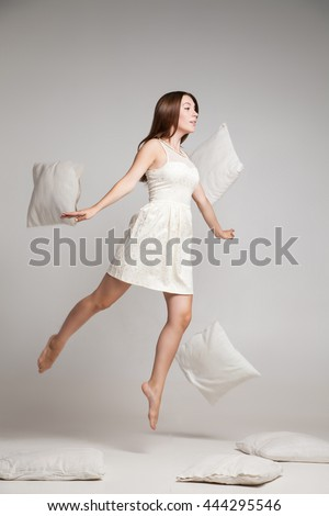 Woman in white dress in mid air with flying pillow