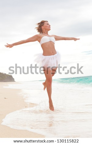 Woman in white dress jumping on beach, feeling freedom - stock photo