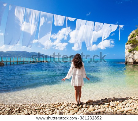 woman in white dress standing on beach - stock photo
