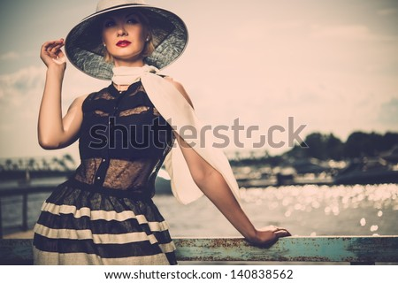 Woman in white hat and scarf standing near old pier rails - stock photo