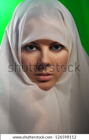 woman in white hijab on green background looks in camera