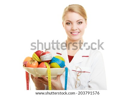 Woman in white lab coat holding fruits and colorful measure tapes isolated. Doctor dietitian recommending healthy food. Diet. - stock photo