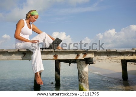Woman in white looking at a laptop on a tropical boardwalk - stock photo