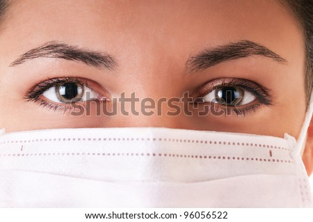 Woman in white medical mask. Selective focus on eyes. - stock photo