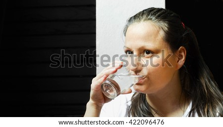 Woman in white shirt drinking the water, against the black background - stock photo