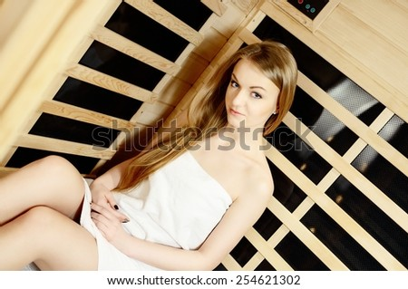 woman in white towel relaxing in wooden sauna room - stock photo