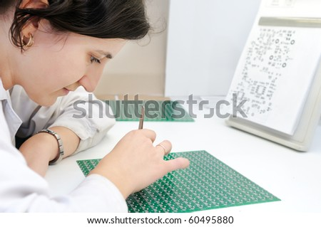 Woman in white uniform checking or assembling components and chip on integrated microcircuit - stock photo