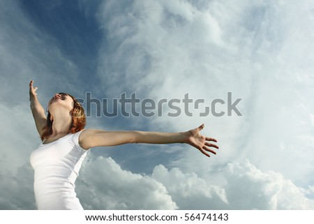 Woman in white with raised hands over airy sky background