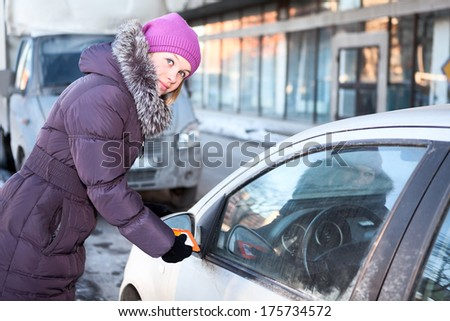 Woman in winter clothes cleaning car windows and mirrors before the trip - stock photo
