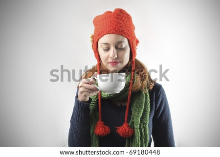 Woman in winter clothes holding a bowl of hot drink - stock photo