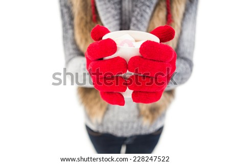 Woman in winter clothes holding a mug on white background - stock photo