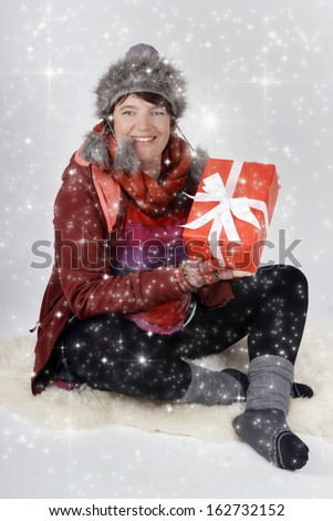Woman in winter clothes with christmas present and white snowflakes - stock photo
