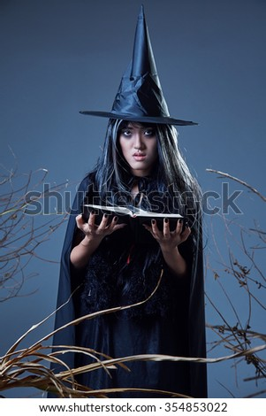 woman in witch costume holding a spell book  - stock photo
