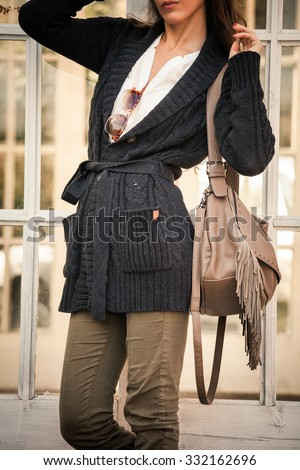 woman in worm dark wool sweater,  black leather high boots hold leather hand bag with tassels   stand in front glass door, closeup, outdoor shot - stock photo
