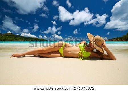 Woman in yellow bikini lying on tropical beach at Seychelles - stock photo