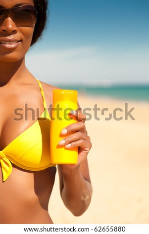 Woman in yellow bikini offering suncream on the beach in order to avoid sunburn, FOCUS is on hand, lots of copyspace - stock photo