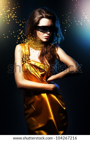 woman in yellow dress and black mask with broken jewelry - stock photo
