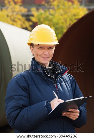 Woman in yellow hard hat taking notes while standing in a construction site - stock photo