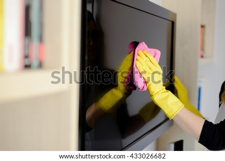 Woman in yellow rubber gloves cleaning tv with pink cloth