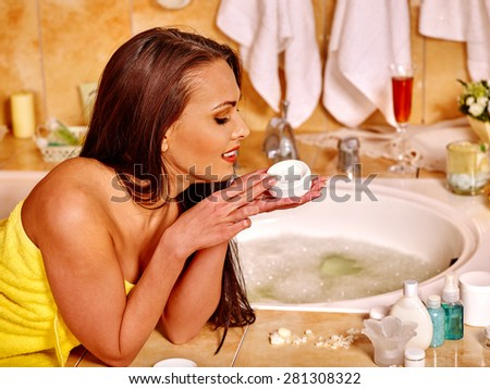 Woman in yellow towel applying moisturizer at bathroom. Visible legs. - stock photo