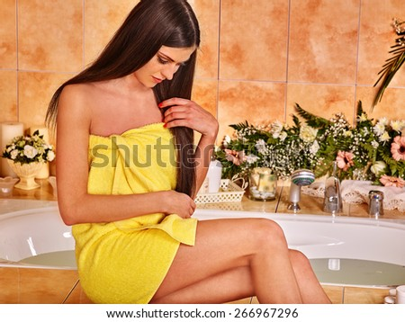 Woman in yellow towel relaxing at flower water spa. - stock photo