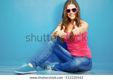 woman in youth style sitting on a floor show thumb up. - stock photo