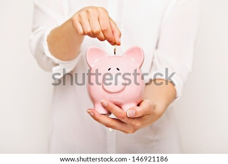 Woman inserting coin in a piggy bank - stock photo