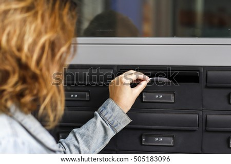 Woman inserting letter in a house's mailbox