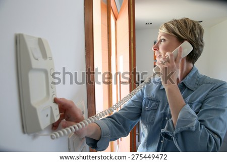 Woman inside home answering intercom - stock photo