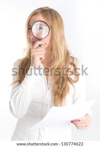 Woman inspecting closely a document through a magnifying glass - stock photo