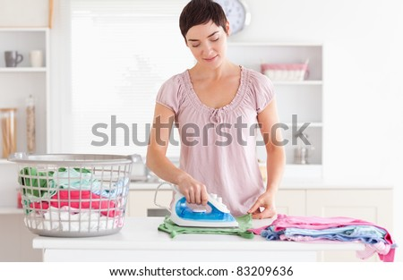 Woman ironing clothes in a utility room - stock photo