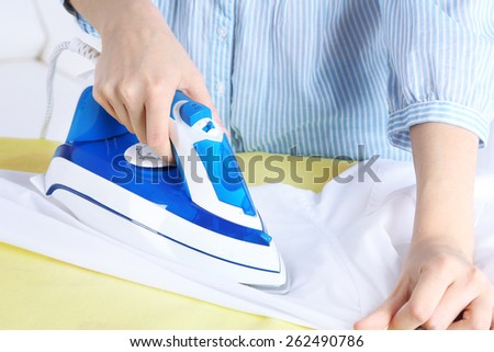 Woman ironing shirt on ironing board in room - stock photo