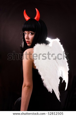 Woman is an angel and  devil. Sexy Halloween devil girl witch on dark background. Beautiful woman with Devil horns. Portrait of young woman dressed as pretty angel. - stock photo