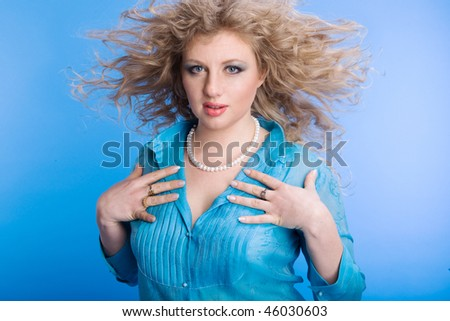 Woman is blown with a wind on a blue background - stock photo