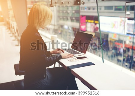 Woman is booking on-line via net-book hotel for rest in weekend, while is sitting with take away coffee in modern cafe. Young female designer web sites is working on her new project on laptop computer - stock photo