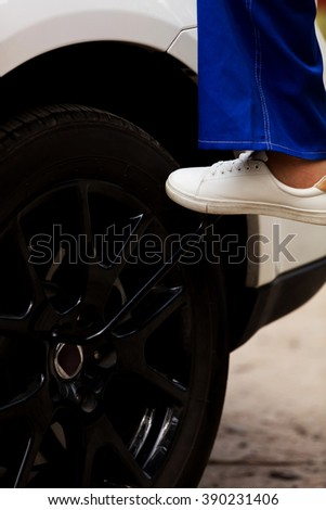 Woman is changing tire of car with wheel wrench - stock photo