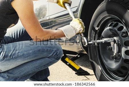 Woman is changing  tire of her car with wheel wrench.