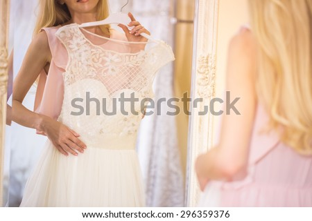 woman is choosing a wedding dress in the shop - stock photo