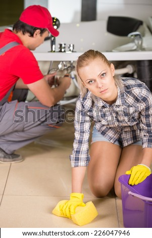 Woman is cleaning the floor in the bathroom, while plumber repairs the pipes. - stock photo