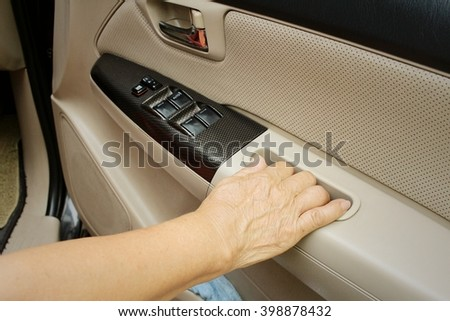 Woman is closing the car door in a car.
