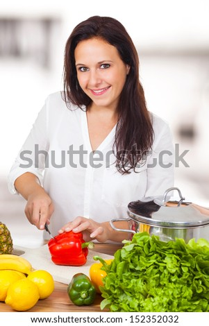 Woman is cooking healthy in the kitchen - stock photo