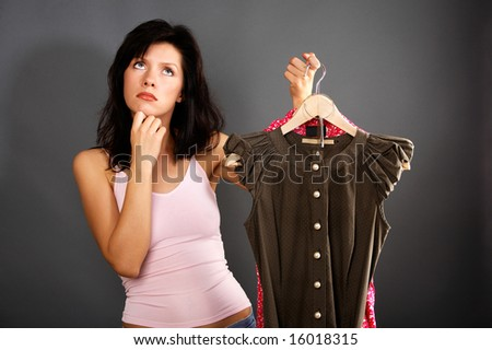woman is deciding which dress to buy