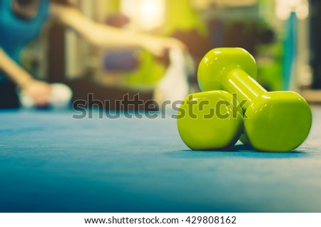 Woman is doing stretching at gym. Close up and focus on a pair of weights - stock photo
