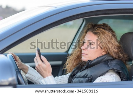 woman is driving her car vand reading a message on her mobile - stock photo