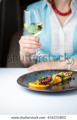 Woman is eating an octopus and drinking wine in a restaurant. Restaurant food concept.