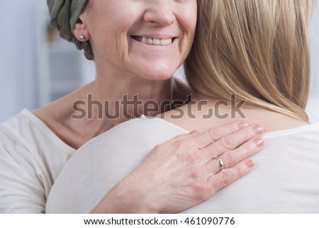 Woman is gentle hugging her daughter with a smile